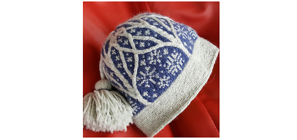 knit hat with blue background, grey stranded designs, and raised grey tree motifs