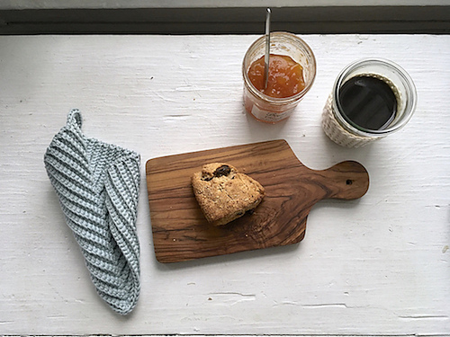 a birds-eye view of a table-top, with a crocheted potholder, a cutting board with a scone, a jar of jam, and a drink